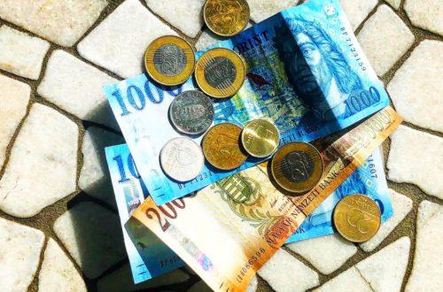 Három papírpénz a földön. Kettő darab ezer forintos, és egy darab kétezer forint. Rajtuk aprópénz hever szétszórva.