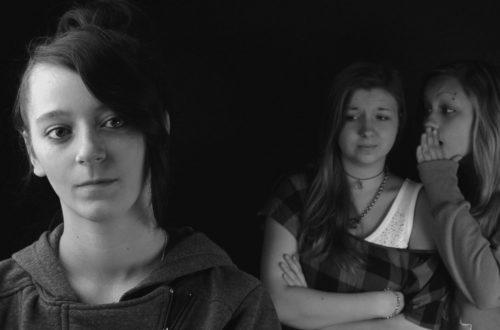 Egy lány akinek háta mögött két másik lány sugdolózik. Összesűgnak a hátad mögött, kibeszélik.